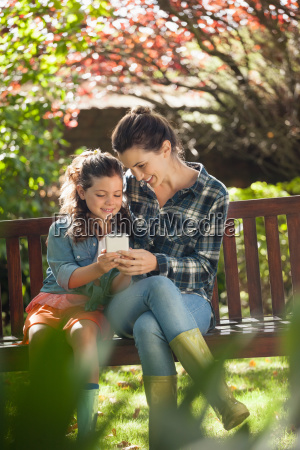smiling girl and mother using mobile