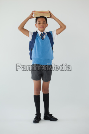 schoolboy holding books on his head