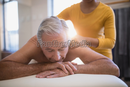 shirtless male patient lying on bed