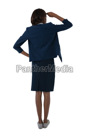 rear view of businesswoman shielding eyes
