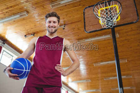 male basketball player standing by basketball