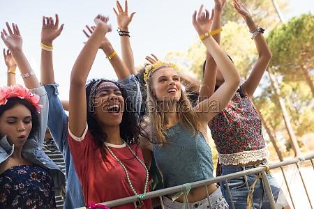 cheerful female fans enjoying at music