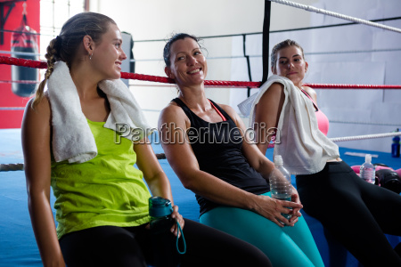 smiling young female athletes leaning on
