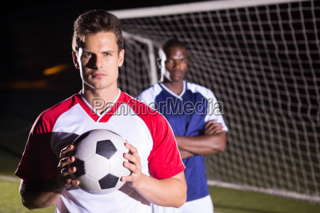 portrait of confident soccer player holding