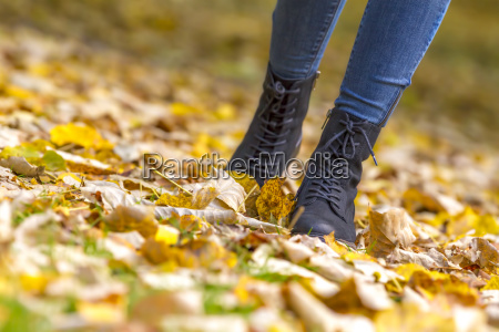 female legs in boots on autumn