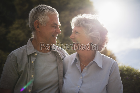 smiling senior couple looking at each