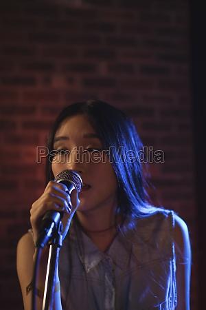 beautiful female singer singing at music