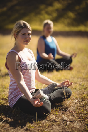 women practicing yoga during obstacle course
