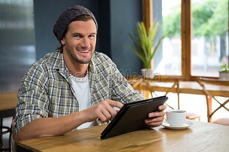 portrait of smiling man using tablet
