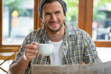 portrait of smiling man holding coffee