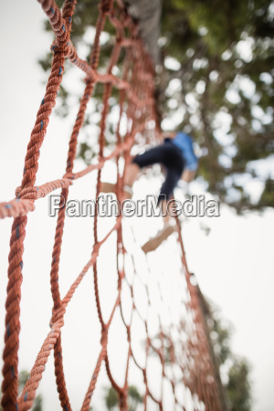 woman climbing a net during obstacle