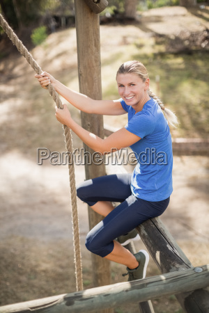 smiling fit woman climbing down the