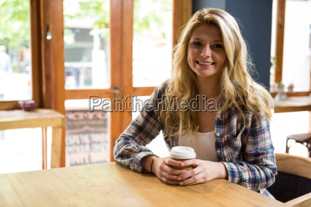 smiling young woman holding disposable coffee