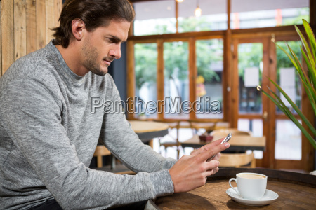 handsome man using smartphone at table