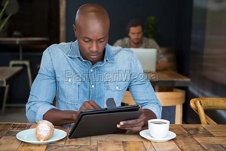 man using tablet computer at table