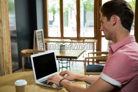 man using laptop at table in