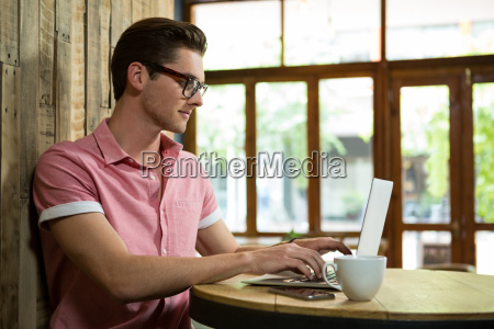 handsome young man using laptop at