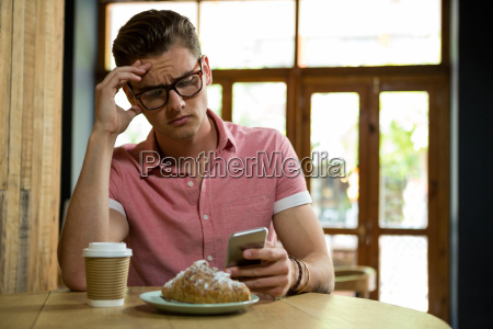 tensed man using smart phone in