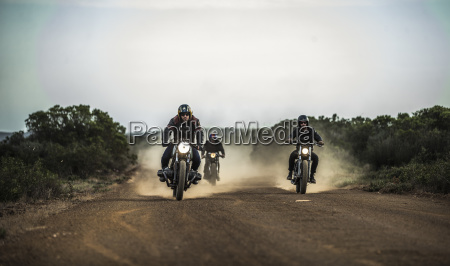 three men riding cafe racer motorcycles