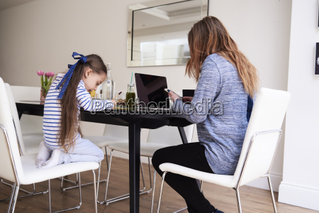 little girl drawing at table while