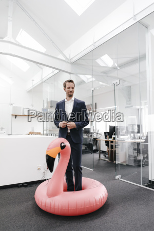 businessman in office with inflatable flamingo
