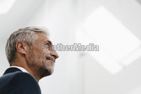 confident mature businessman looking up