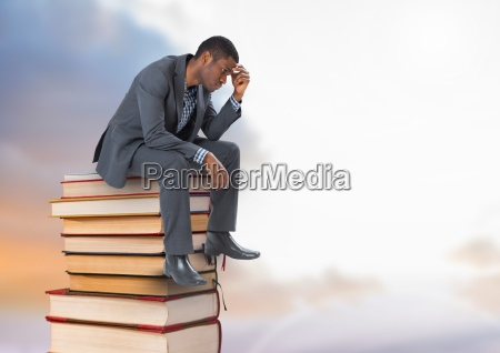 businessman sitting onbooks stacked by cloudy