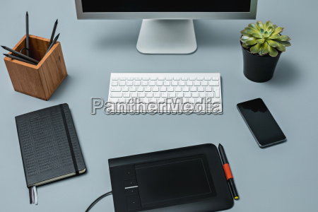 the gray desk with laptop notepad