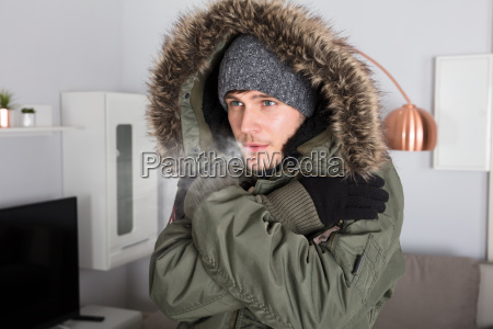 man with warm clothing feeling the
