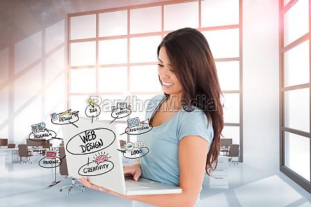 smiling businesswoman web designing on laptop