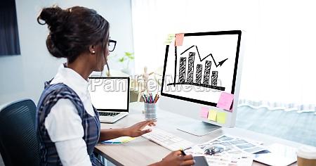 businesswoman analyzing graph on desktop computer