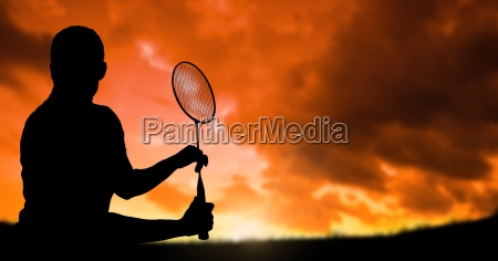 silhouette man playing badminton against cloudy