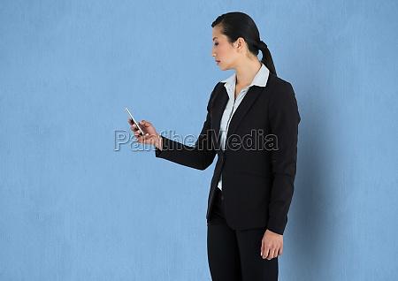 businesswoman using smart phone against blue