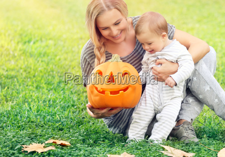 happy mother with baby in halloween