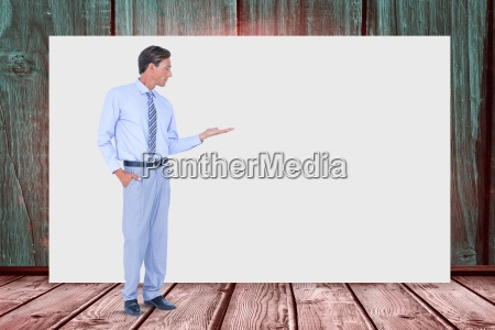 businessman gesturing while standing against blank