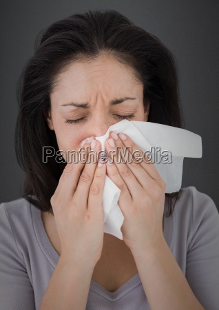 woman crying into tissue against grey