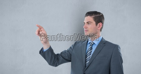 businessman touching imaginary screen over gray