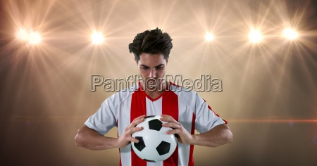 soccer player holding ball at illuminated