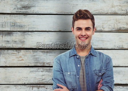 handsome man smiling against wooden wall