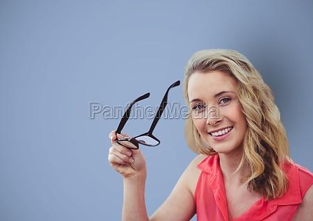 smiling businesswoman holding eyeglasses over blue