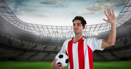 soccer player with arm raised holding