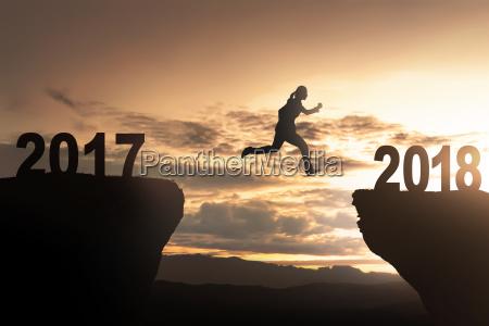 silhouette of woman jump toward 2018
