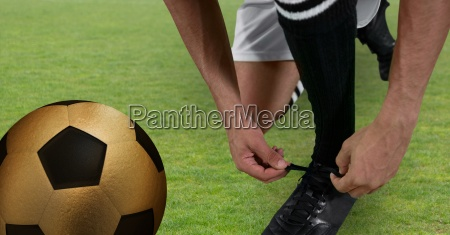 soccer player tying his shoes with