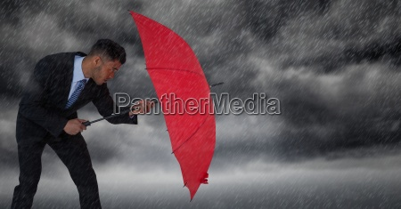 business man blocking rain with umbrella