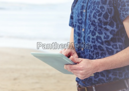 trendy man mid section with tablet