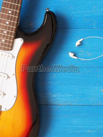 vintage guitar with earphones on wood