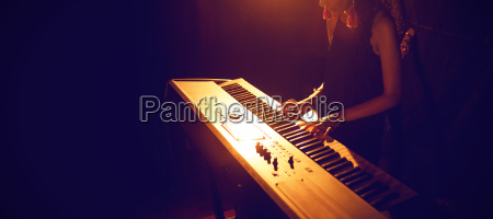 female musician playing piano keyboard in