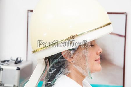 woman under a professional hair steamer