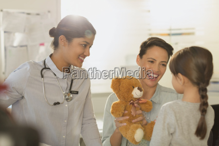 smiling female pediatrician and mother showing