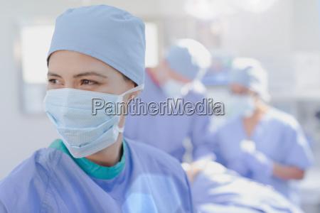 smiling female surgeon wearing surgical mask